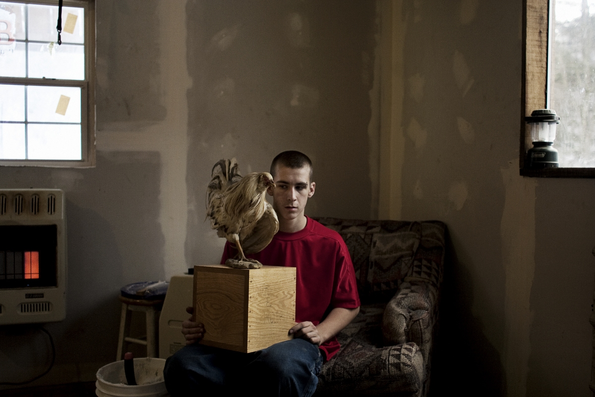 Tylor Woodrum, 16, holds a box containing his father's ashes on January 30, 2007 in Carbondale, Ohio. Dave Woodrum was killed in August of 2006 in a high-impact 4-wheeler accident. Dave's family had his body cremated and his favorite cock-fighting rooster mounted on top of the box.