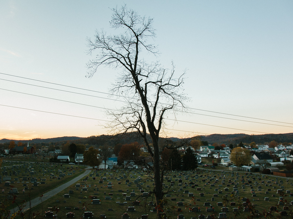 Power lines, Tree, Gravestones, Houses, Hills