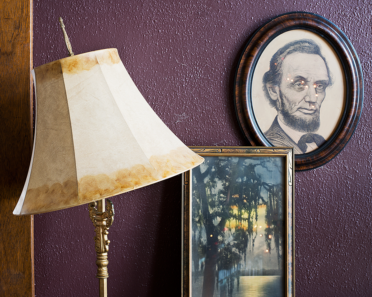 """Twinkle"", Archival Pigment Print, 22x27"" and 28x34"", 2012. Home display of my mother's portrait of Lincoln, reading lamp, and print of a southern bayou landscape at Christmas, (Grand Island, NE)."