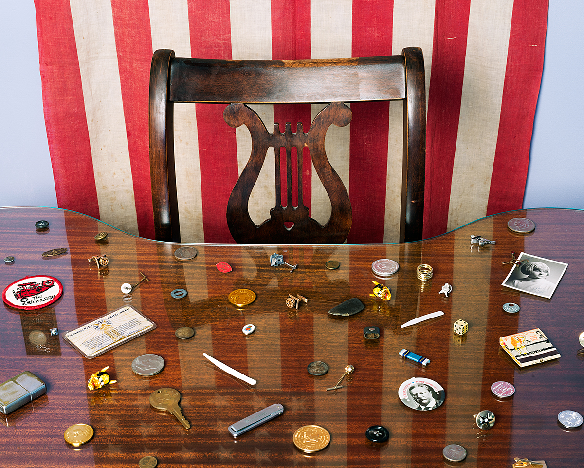 """Memory Box"", Archival Pigment Print, 22x27"" and 28x34"", 2013. My father's collection of ""memory objects"", spread out on my mother's desk with reflection of the American flag (Grand Island, NE)."