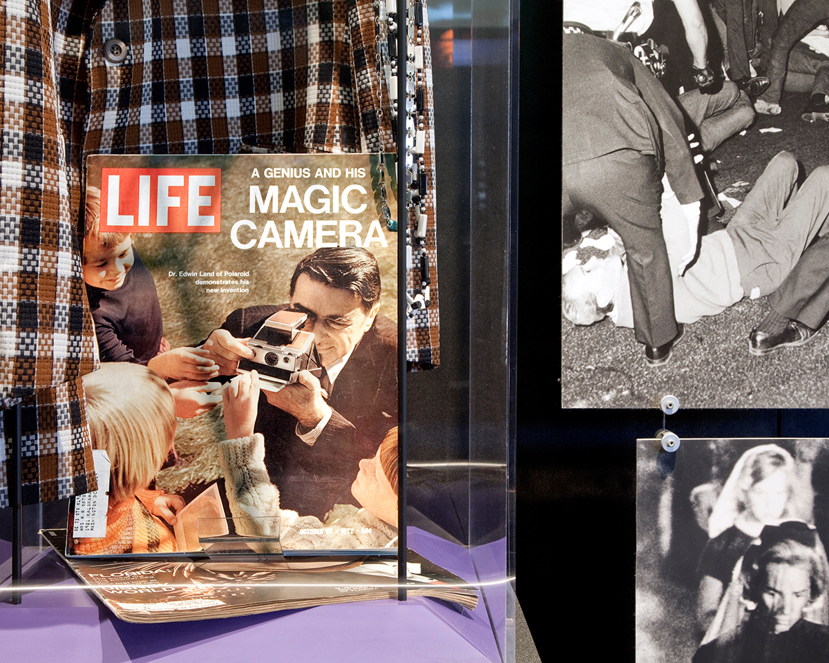 """Magic Camera Riot"", Archival Pigment Print, 22x27"" and 28x34"", 2012. A display featuring 1970s fashion and Edward Land featured in LIFE Magazine alongside photographs of race riots and JFK's funeral, Gerald R. Ford Presidential Museum (Grand Rapids, MI)."